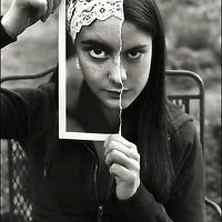 A young woman holding a photograph infront of her face
