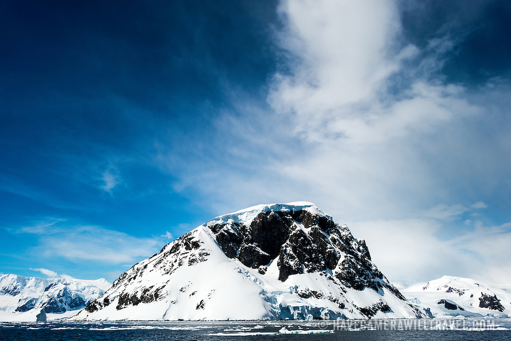 A rocky domed mountain covered in snow and ice against a blue sky on a clear sunny day near Cuverville Island, Antarctica.