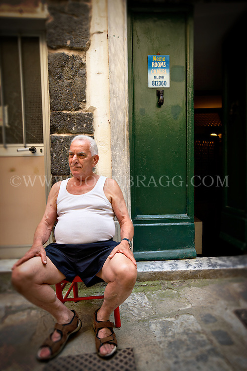 An elderly man sitting in Vernazza, Italy.