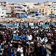 Northern african would- be immigrants queue for food in the portual area of Lampedusa.The Island is currently overpacked with more than 6000 immigrants living in critical sanitary and igienic condition.
