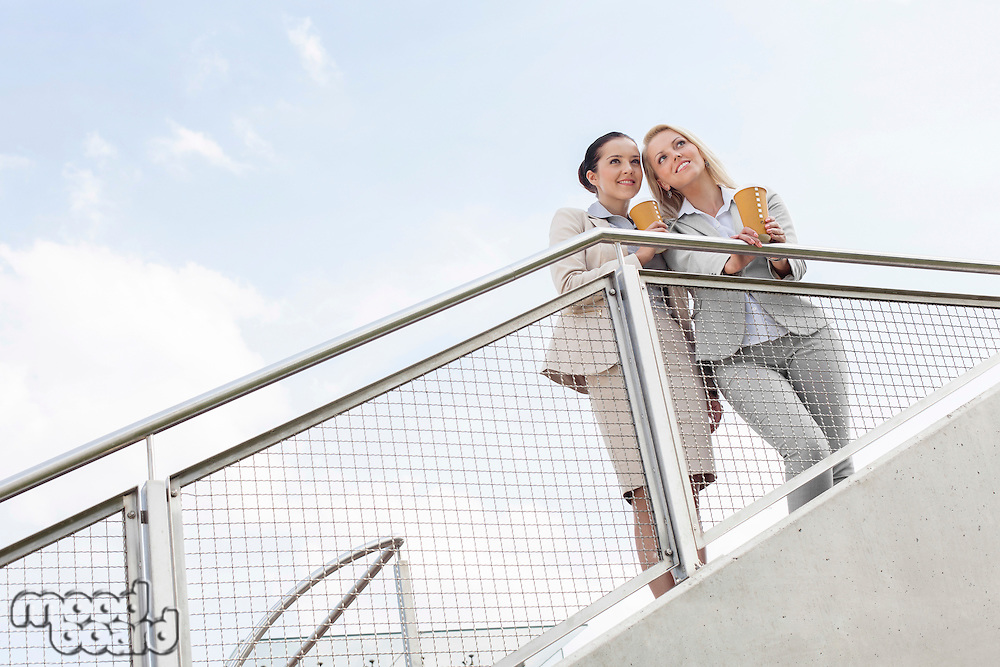 Low angle view of young businesswomen with disposable coffee cups standing by railing against sky