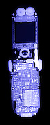 An x-ray of a cell phone showing the speakers at the top, a digital camera inthe center, and the dense circuitry required to send and receive radio signals.