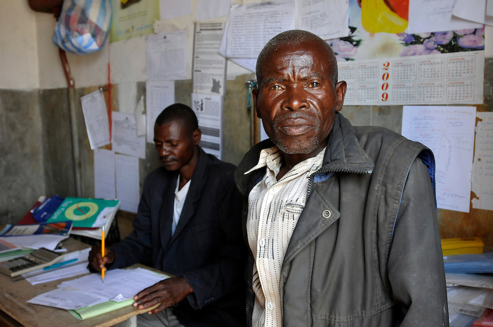 Fernando Enoque Chissuale (left), school director, and the guardian in the office of the Lumege-Canjamba primary school. The area around the school was contaminated with landmines during Angola's long civil war, preventing many children from coming to school and limiting the movement of those who did. Mines Advisory Group (MAG) cleared the area of mines and other remnants of war allowing children to receive an education safely and for plans to build more class rooms to accomodate an increasing number of students who are arriving under the government's Village Reunification Program - a program that encourages families living in remote hamlets to move to larger villages so that the government can provide basic services such as education, health care, water and electricity. .Lumege Canjamba, Angola. 30/09/2010.Photo © J.B. Russell