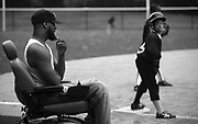 Coach Rock coaches third base as Rahkeem Wright waits for the signal to run for home in the team's win over the Black Yankees at Weequahic Park.