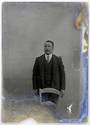 eroding glass plate with an adult man standing in front of a wall