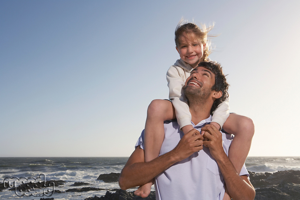 Father giving daughter piggyback half length in front of ocean