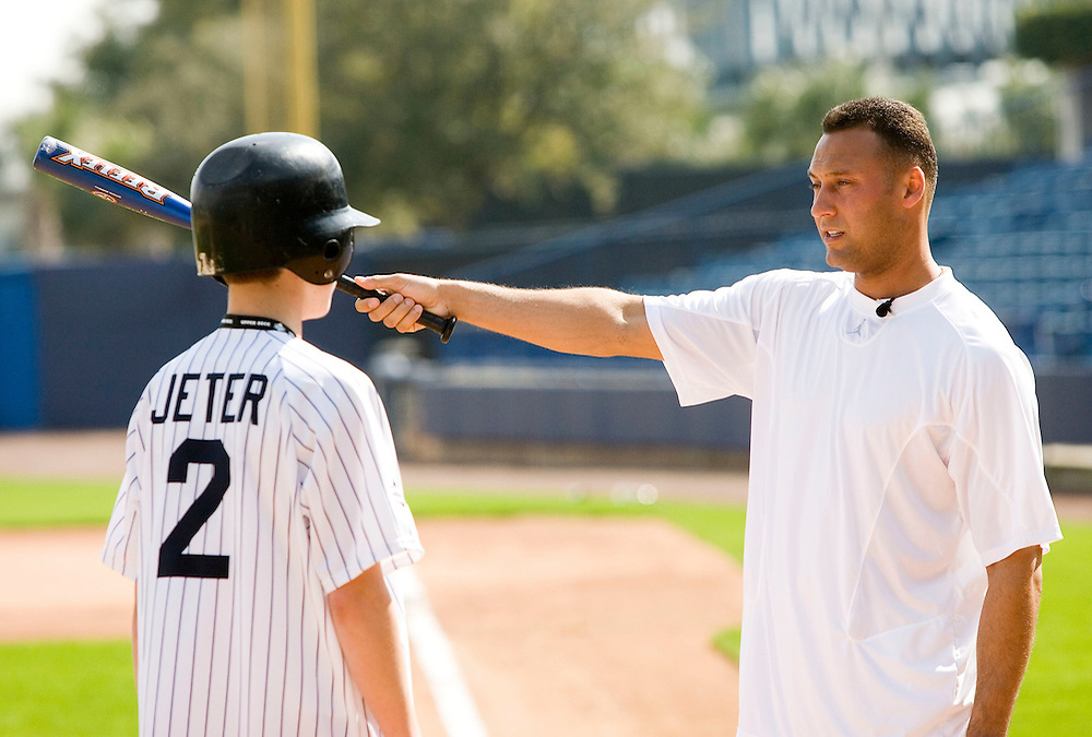 """New York Yankee's Derek Jeter, right, gives instruction to Justin Topa, 15, of Binghampton, New York during the Upper Deck, """"Play Ball! with Derek Jeter"""" clinic on Saturday, February 10, 2007 at Legends Field in Tampa, Florida.  Justin Topa, 15, of Binghampton, New York, Jordan Boone, 10, of Las Vegas, Nevada, Bryce Porter, 10, of Costa Mesa, California and Gavin Leonard, 9, of Bristol, Virginia, each won the grand prize to meet Jeter through various promotions on www.UpperDeckKids.com in 2006. UPPER DECK/Scott Audette"""
