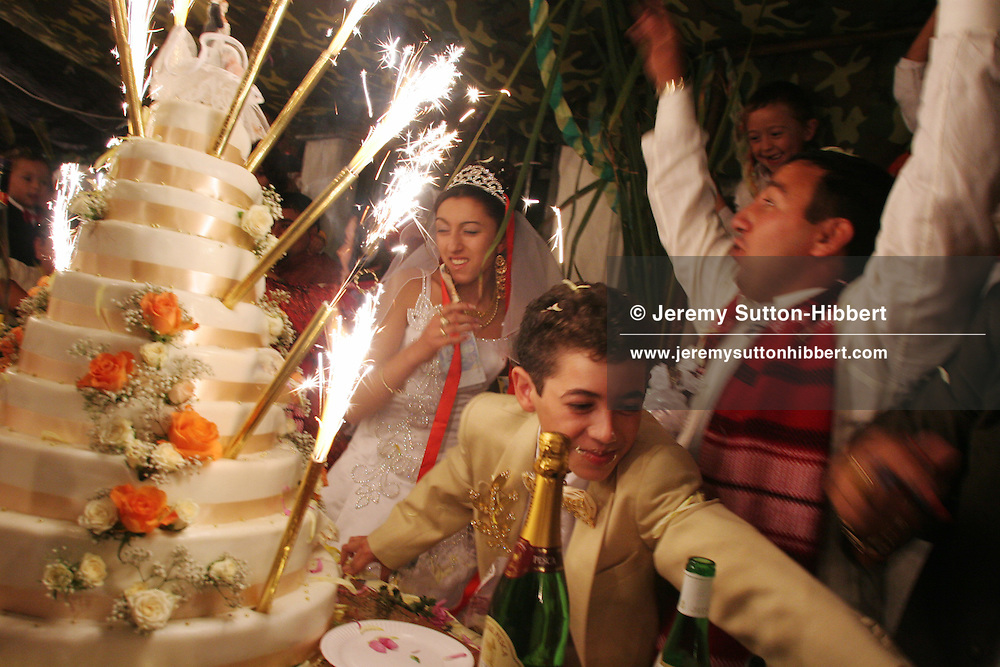Sparkling candles are lit on the wedding cake on the second evening of wedding celebrations for the marriage between Roma (gypsies)  Garoafa Mihai (on left), aged 14, and Florin 'Ciprian' Lulu (centre, foreground), aged 13, in the village of Sintesti, Romania, on Sunday, Sept. 24th 2006. Their partnership was decided by their parents and not through love, and under Romanian law is illegal. The children will neither complete legal paperwork for the wedding, nor visit the local Romanian Orthodox church for a blessing. On her wedding day Garoafa wore approximately 30-40,000 USD of gold Franz Josef coins on her dress, part of the large dowry that she takes with her as she begins her married life. For the guests and for the people of the village another 30,000 USD of pigs, approximately 100,  were killed to be eaten and given away as presents of food. Another 30,000 USD was spent on famous Roma musicians to come and sing 'manele'  type music at the wedding extolling the wealth and status of their patrons for the weekend in their songs.  24th Sept 2006