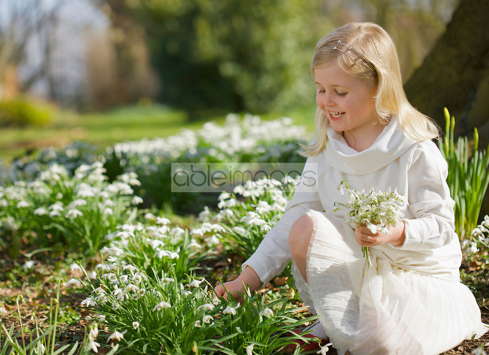 Portrait of a smiling young girl picking snowdrops