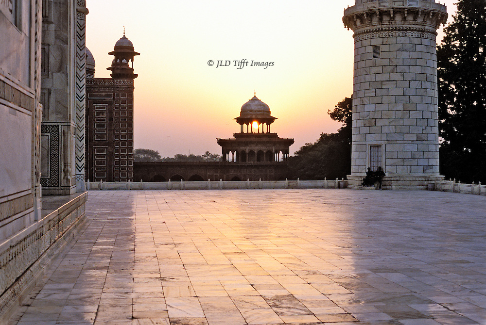 Taj Mahal terrace, looking east at sunrise, up the Jumna River.  The white marble terrace emits an orange glow from the rising sun.  Chhatri of the adjoining han in the complext in silhouette.