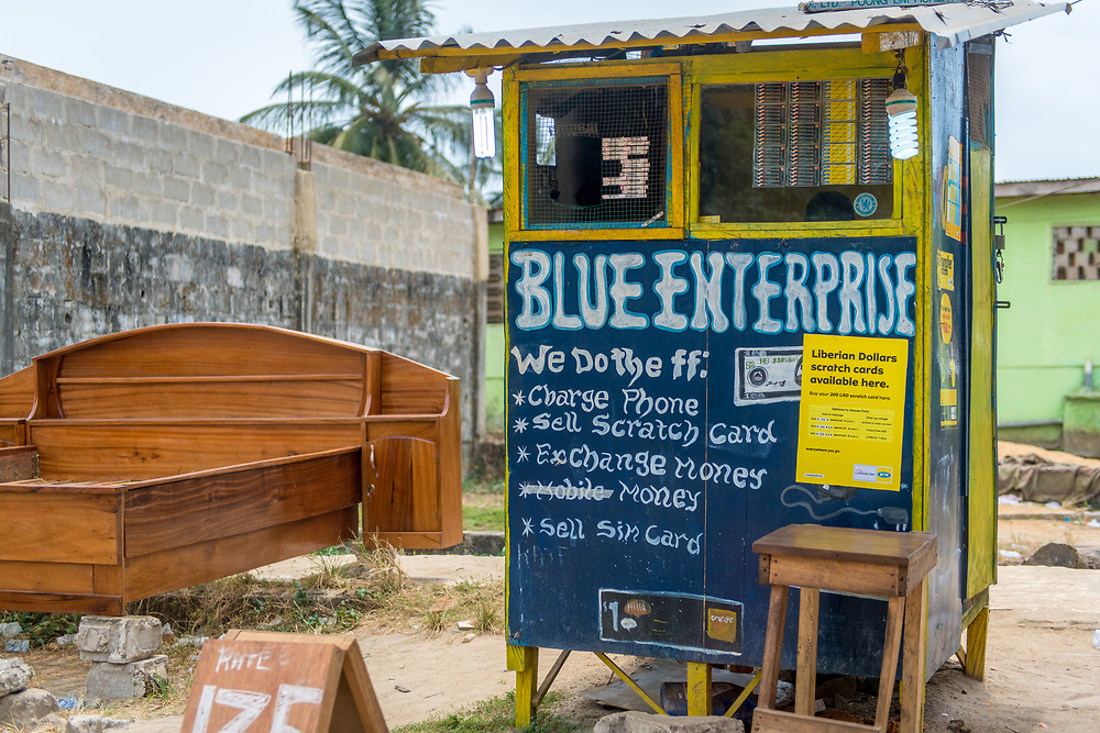 A booth advertising the sale of various services and items, including scratch cards. Monrovia, Liberia