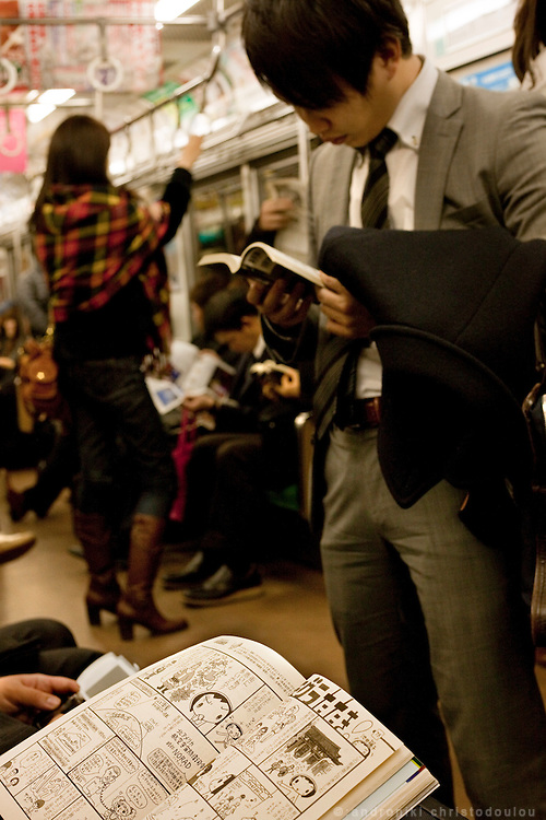 Man reading a manga in the Tokyo metro car