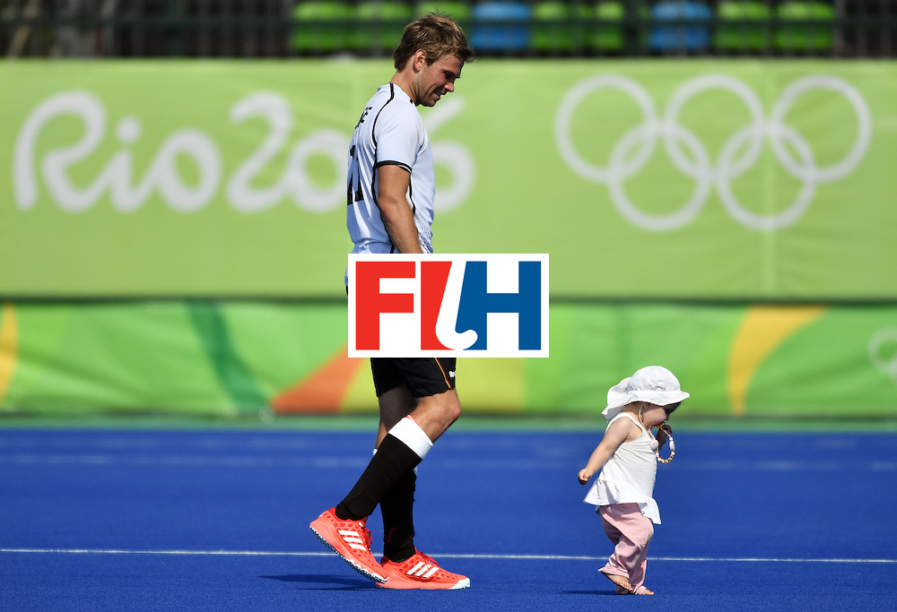 Germany's Moritz Furste walks on the pitch with his child after winning the men's Bronze medal field hockey Netherlands vs Germany match of the Rio 2016 Olympics Games at the Olympic Hockey Centre in Rio de Janeiro on August 18, 2016. / AFP / Pascal GUYOT        (Photo credit should read PASCAL GUYOT/AFP/Getty Images)