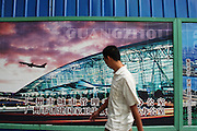 1 August 2007 - Guangzhou, China - A Chinese man walks past a billboard promoting the new Guangzhou International Airport. Photo Credit: Luke Duggleby