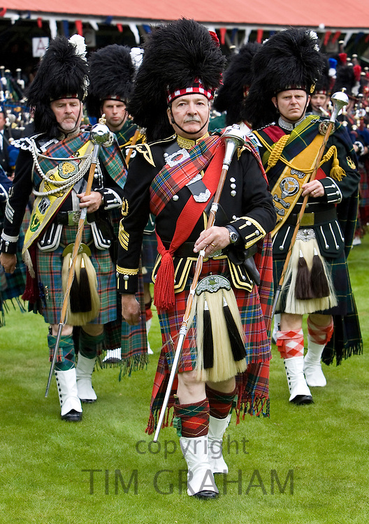 Drum Major leads band of Scottish pipers at Braemar Games Highland Gathering, Scotland