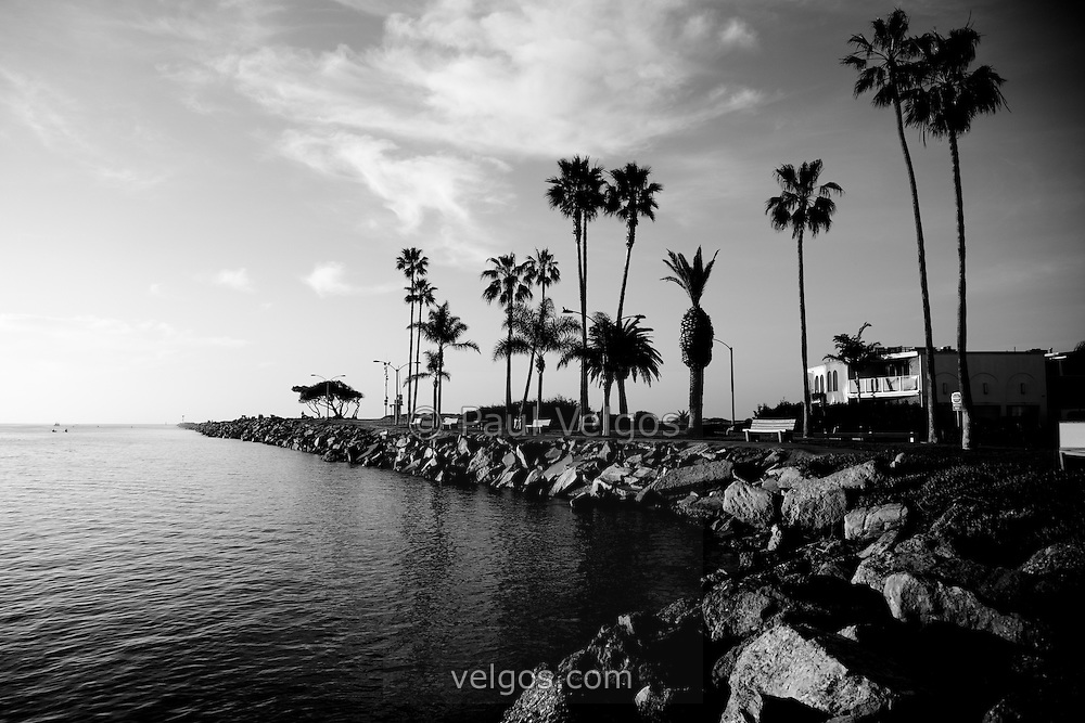 Black and white photo of the Newport Beach Jetty taken at West Jetty View Park at Peninsula Point. The Jetty is located at the end of Balboa Peninsula where Newport Bay meets the Pacific Ocean. The opening scene of Gilligan's Island was filmed here where the Minnow heads out to sea. Newport Beach is a beach community in Orange County Southern California.