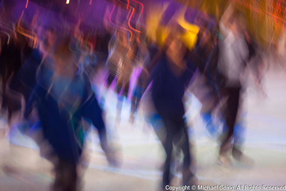 Motion blur of a group of ice skaters at night