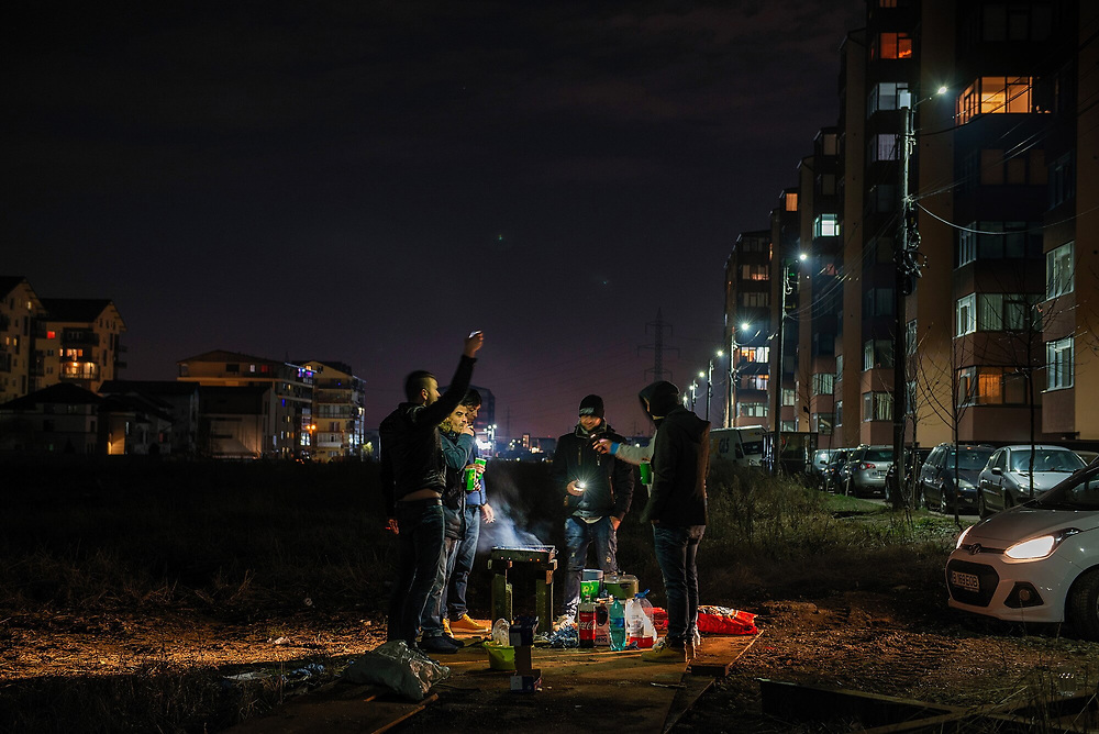 People prepare a barbeque as they celebrate New Year at a new residential complex in Militari on the periphery of Bucharest.