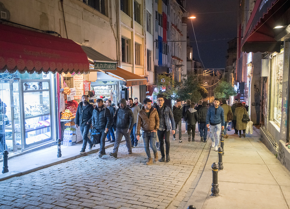 A group of people make their way uphill on small street at night in the city of Istanbul, Turkey