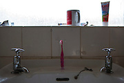A pink child's toothbrush sits on the sink in the family bathroom. Leyland, Lancashire.