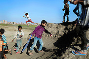 A boy is jumping while others are about to start a game of cricket around the abandoned evaporation pool (left) that was once used by Union Carbide (now DOW Chemical) next to their industrial complex, site of the infamous 1984 gas tragedy in Bhopal, Madhya Pradesh, central India. The poisonous cloud that enveloped Bhopal left everlasting consequences that today continue to consume people's lives. Thousands tons of hazardous chemical waste are still buried in various spots around this area of Bhopal.