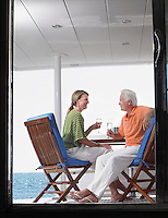 Middle-aged couple drinking wine on yacht profile view through door