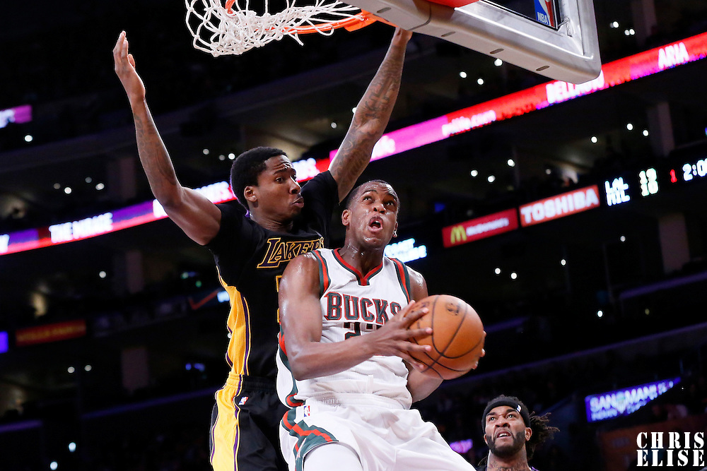 27 February 2015: Milwaukee Bucks guard Khris Middleton (22) goes for the reverse layup past Los Angeles Lakers forward Ed Davis (21) during the Los Angeles Lakers 101-93 victory over the Milwaukee Bucks, at the Staples Center, Los Angeles, California, USA.