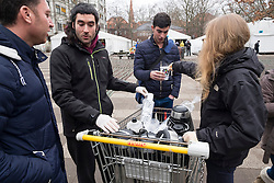 © Licensed to London News Pictures. 18/03/2016. Local social volunteers hand out hot drinks to refugees registering at the Regional Office for Health and Social Affairs Berlin(LaGeSo).  A total of 1.1 million people were registered as asylum-seekers in Germany in 2015, nearly five times the number registered in 2014. More than a third of these, nearly 430,000 people, were those fleeing the protracted civil war in Syria. Berlin, Germany. Photo credit: Ray Tang/LNP