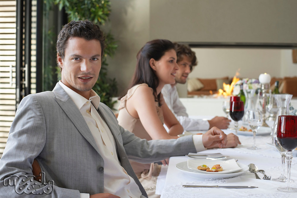 Young stylishly dressed man sitting at table of formal dinner party smiling