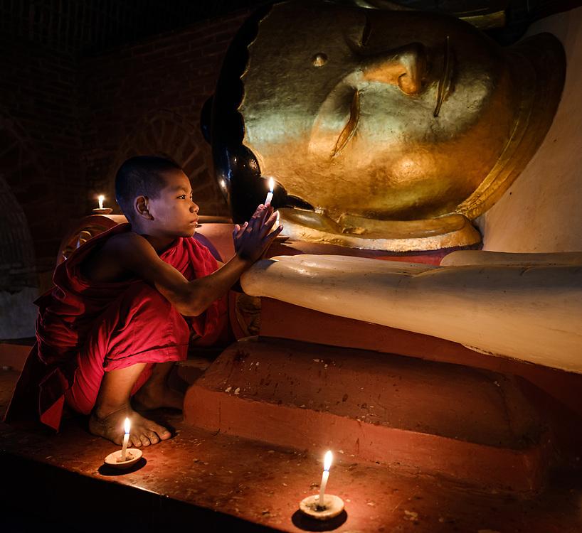 BAGAN, MYANMAR - CIRCA DECEMBER 2017: Young monk lighting candles in a temple in Bagan