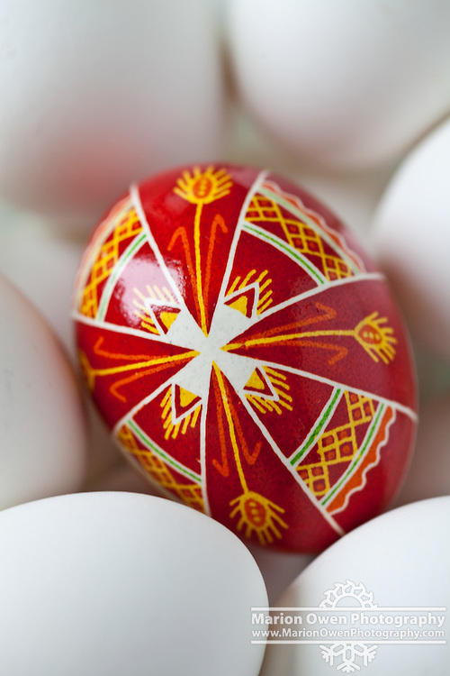 Closeup of traditional style Pysanky or Ukraine Easter egg, nestled in bowl of white eggs, handmade by Orthodox nun, Kodiak Island, Alaska.