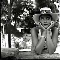 A young woman wearing a hat and sunglasses resting