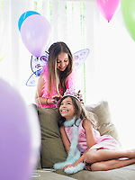 Two girls (7-9 10-12) on sofa in party costumes one adjusting other's tiara