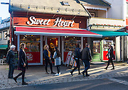People talking outside Sweet Heart sweet shop, Storgata, Tromso, Norway