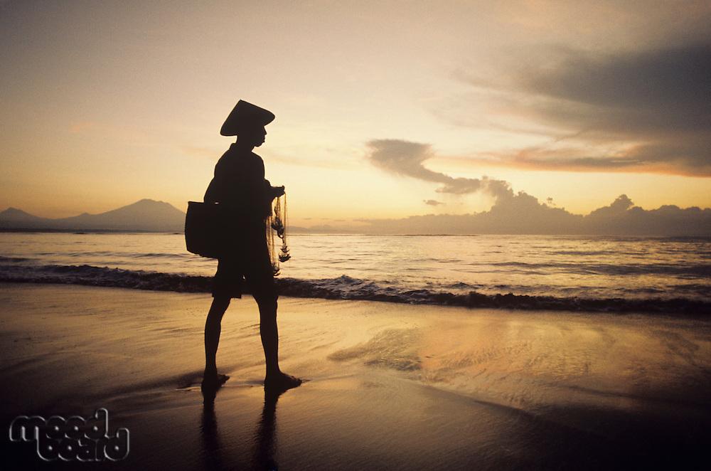 Asian fisherman on shore watching sunset