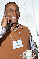 Business man using mobile phone in office, portrait