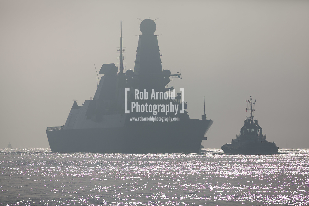 HMS Dragon sails through the mist into her home port of Portsmouth for the first time in two months.  The Type 45 destroyer has been on a deployment involving exercises with the U.S. Navy and also a visit to the British Overseas Territory of Gibraltar.
