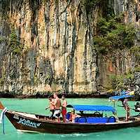 Tourists Riding Longtail in Pileh Cove on Phi Phi Ley, Thailand <br />