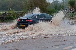 © Licensed to London News Pictures. 26/10/2019. Crickhowell, Powys, Wales, UK. Motorists drive through floodwater on the A4077 near The Vine Tree Inn in Llangattock in Powys near Crickhowell as rain falls relentlessly and the level of the river Usk rises dramatically. Water enters The Bridge End Inn basement in Bridge Street, Crickhowell  in Powys. Photo credit: Graham M. Lawrence/LNP