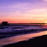 Photo of Newport Beach Pier sunset in Orange County California. Newport Pier is located on Balboa Peninsula and is a popular attraction. Newport Beach is a wealthy beach community along the Pacific Ocean in Orange County Southern California. Photo is high resolution and was taken in 2012.