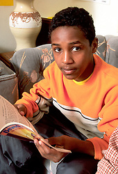 United States, Washington, Seattle, boy (age 13) reading book on couch