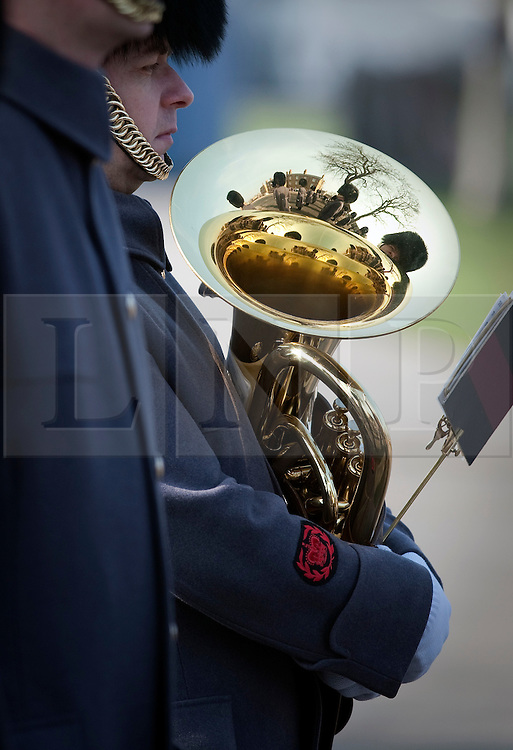 © Licensed to London News Pictures. 01/03/2012. Hounslow, UK. Reflected in a Musicians trombone from the Welsh Guards band as they watch HRH Prince Charles Presenting leeks to 1st Battalion Welsh Guards at Cavalry Barracks,  Hounslow, London on St David's Day, March 1st, 2012.  Two-thirds of the Battalion's 600 soldiers are due to be deployed to Afghanistan in the next two weeks. Photo credit : Ben Cawthra/LNP