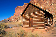 Red sandstone cliffs above the old school house in the pioneer town of Fruita, Capitol Reef National Park, Utah