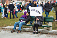 A man and child sit next to a protestor with a sign on Boston Common during the March for Our Lives
