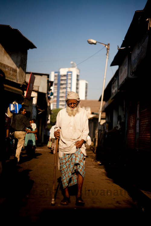 "An elderly man walks trough the streets, in the Daharavi slum area in Mumbai, India, on Feb. 4, 2009. A sprawling slum area in the heart of the fastest growing city in the world, Dharavi and its affiliate slum areas have been thrust into limelight in the year 2008 like never before. Earlier it was the slum redevelopment authorities who threatened to break down the shanties and build new infrastructural projects, and during the far end of the year it was the movie ""Slum Dog Millionaire"". Winning Gloden Globes, 8 Oscar's & 7 Bafta's the movie has bought to light the ruggedness and the struggle of the life in the slums of Indian cities. While the movie is a fairy tale story of positive endings the real hardship, unemployment and economic disparities seen in the slums is striking and deplorable. Yet the slums of Mumbai offer hope and oppurtunity to the few who travel and live away from their native villages and try make a living out of India's growth curve and rapid industrial progress. .. 2009 brings with it, recession, downturn and unemployment. In this scenario the life in the slum gets more rugged and difficult. This photo essay is a peek into the daily lives of city slum dwellers who live, hope, dream, relax, enjoy in the premises of these slums at the fringes of progress and development awaiting for an oppurtunity to break free into the other side."