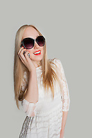 Beautiful girl answering cell phone against gray background
