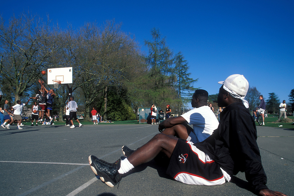USA, Washington, Seattle,  Men watch pickup basketball game in playgrounds at Green Lake Park on Sunday afternoon
