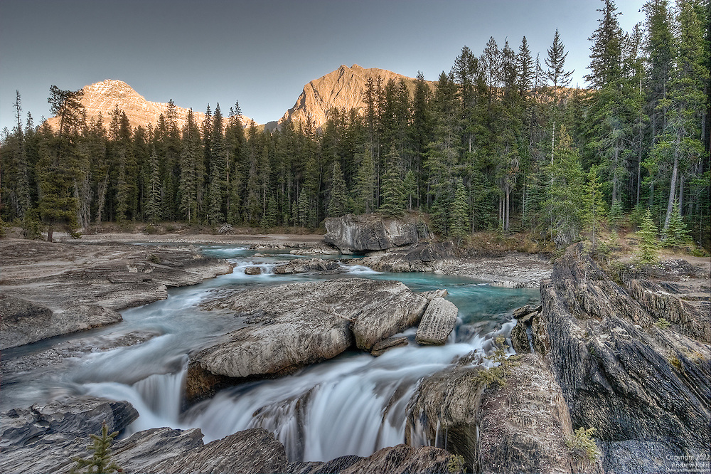 Kicking Horse River at sunset under low flow conditions during the fall with Mount Stephen and Mount Dennis in the distance.  This is a 4-shot stacked HDR image to deal with an intense Dynamic Range.A black and white layer was applied with 25% opacity to this image