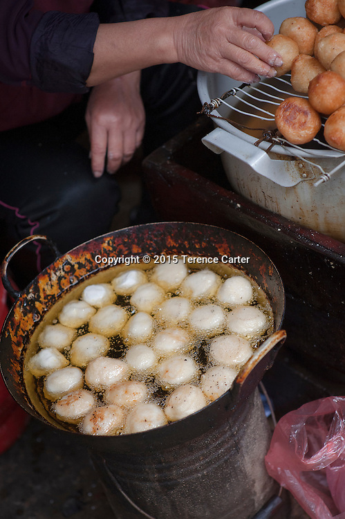 A woman fries banh tieu, or Vietnamese doughnuts in the markets of Sapa, Vietnam.