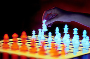 Glowing chess board with hand moving knight.Black light